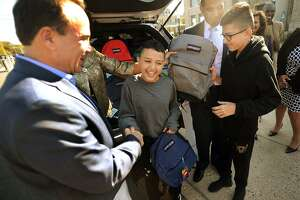 From left; Bridgeport Mayor Joe Ganim gives school backpacks to brothers Juan, 12, and Jan Casiano, 13, from Bayamon, Puerto Rico, outside City Hall in Bridgeport, Conn. on Thursday, October 5, 2017. The brothers, who are staying with Bridgeport relatives following the devastating hurricane in Puerto Rico, will begin attending Luis Munoz Marin School next week.