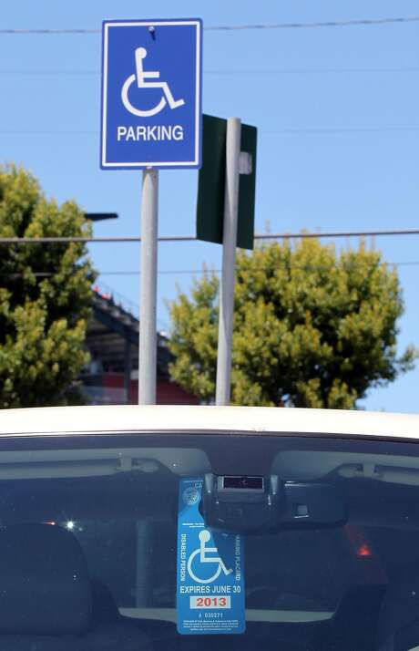 A handicapped placard hangs from the rear view mirror of a car parked outside AT&T Park. Thousands of Cars Park round the Giants stadium on game day allowing dozens of disabled parking permits to be used on a number of limited handicapped spaces Wednesday June 27, 2012 at AT&T Park in San Francisco Calif. Photo: Lance Iversen, The Chronicle