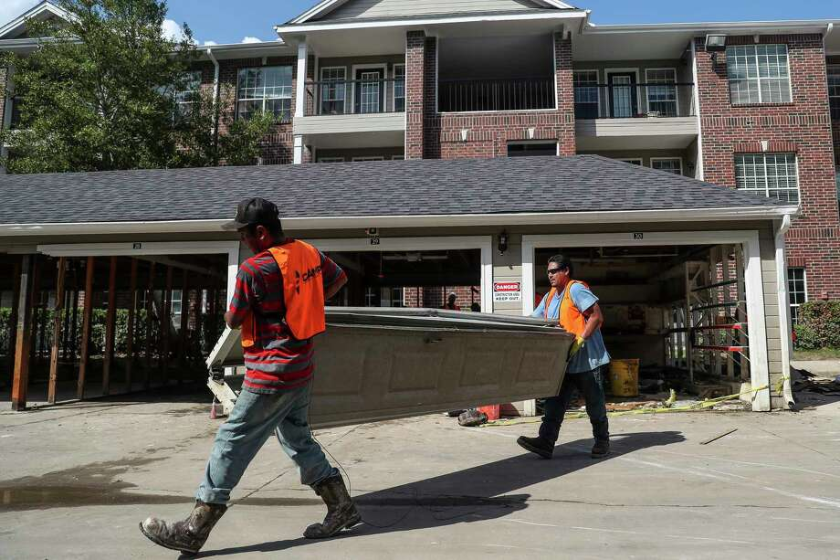 CAMP Construction Services contractors remove the door from a garage at apartment that flooded during Hurricane Harvey.  Photo: Michael Ciaglo, Houston Chronicle / Michael Ciaglo