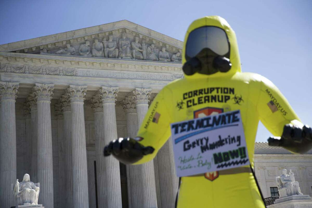 An inflatable hazmat-suited corruption cleanup fighter, brought by demonstrators to the U.S. Supreme Court building as justices heard arguments in a key gerrymandering case, on Capitol Hill in Washington, Oct. 3. On Tuesday, lawyers for the state of Wisconsin urged the justices to reject a challenge to that stateís redistricting map, drawn by the Republican-controlled government. (Tom Brenner/The New York Times) ORG XMIT: MER2017100312484501