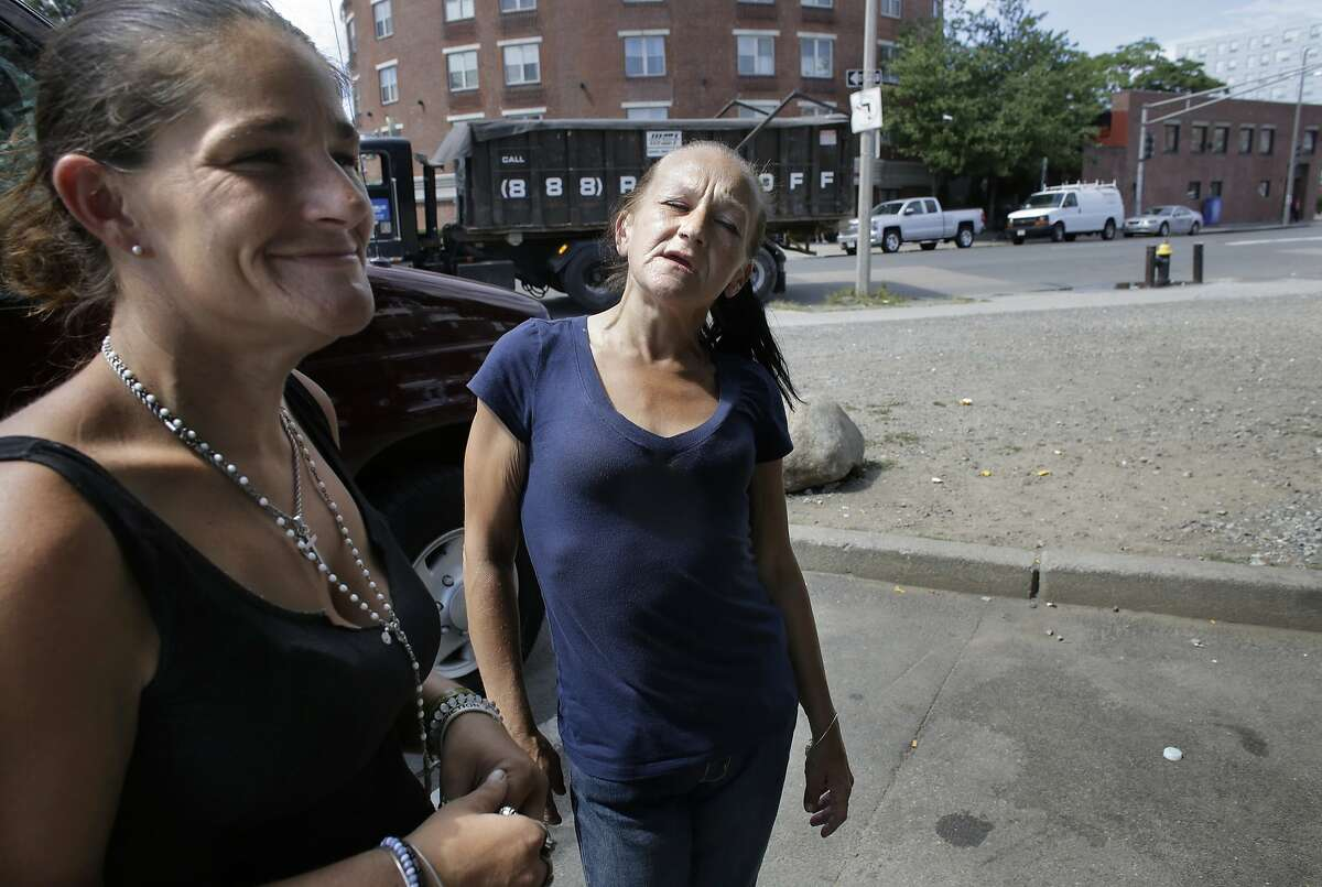 """In this Wednesday, Aug. 23, 2017 photo Jamie Allison, left, stands with a resident of the Mattapan neighborhood of Boston, on the street near a strip of land sometimes referred to as """"Methadone Mile,"""" in Boston. Tobin says she is in a methadone program, and had just come from Narcotics Anonymous meeting when she ran into Allison. (AP Photo/Steven Senne)"""