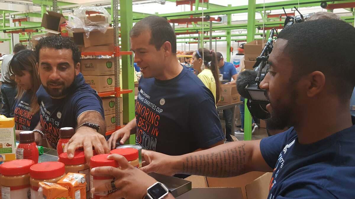 Former Dynamo players Dwayne DeRosario (left), Alejandro Moreno (middle) and Corey Ashe assemble disaster-relief boxes Thursday morning at the Houston Food Bank as part of BBVA Compass' week of service ahead of Thursday's Dynamo Charities Cup between the Dynamo and Cruz Azul at BBVA Compass Stadium.