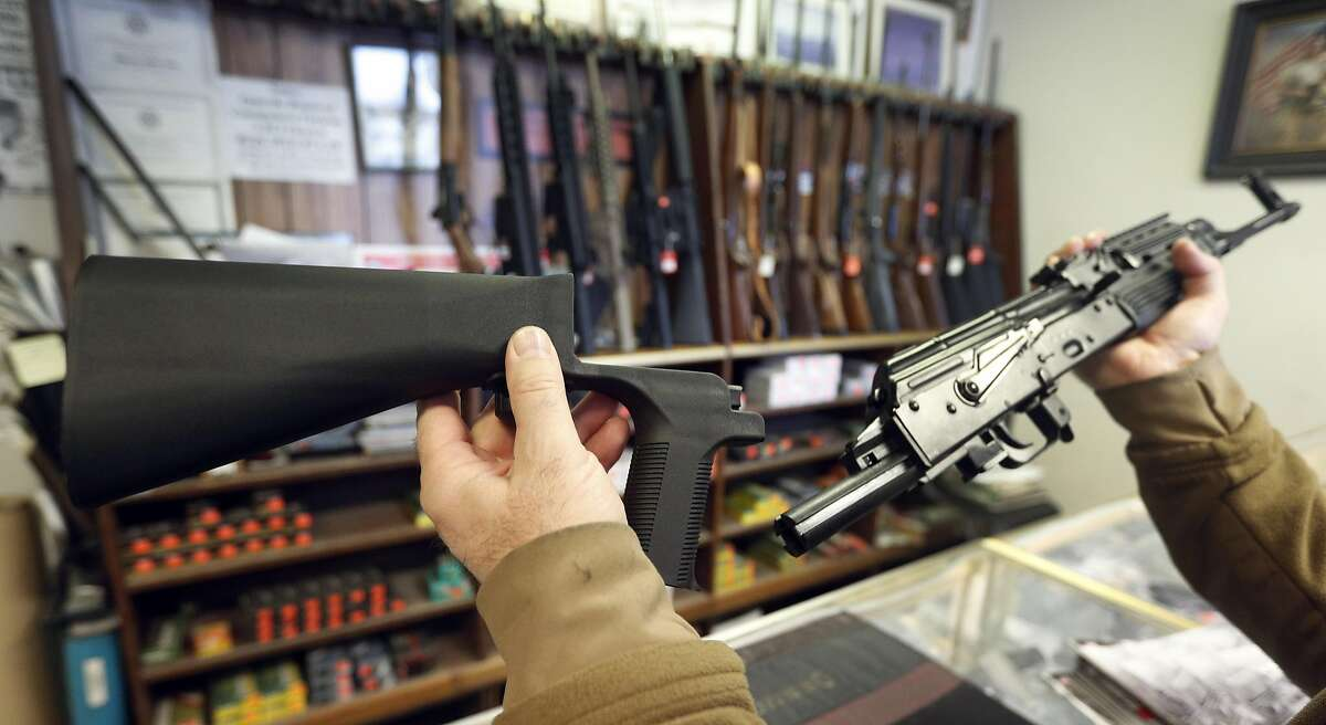 """A """"bump stock"""" device that fits on a semi-automatic rifle to increase the firing speed, making it similar to a fully automatic rifle, is shown next to a AK-47 semi-automatic rifle at a gun store on October 5, 2017 in Salt Lake City, Utah."""