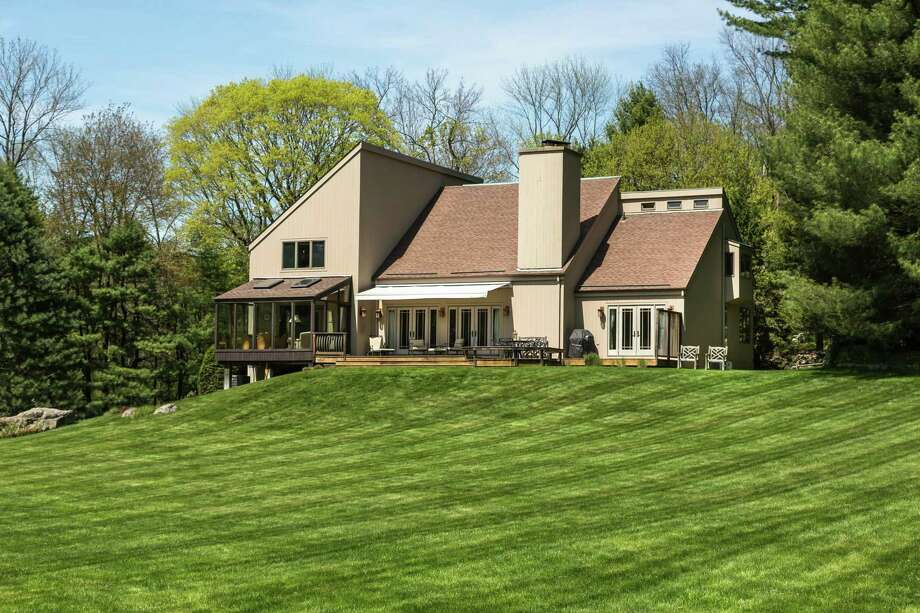 "If there's one word that adequately describes the custom-designed contemporary at 1313 Old Academy Road in Fairfield, it's ""dramatic."" From the sprawling two acres of property on which the 3,830-square-foot home sits, to the vaulted ceilings throughout the house, to the open upstairs walkway that gives a direct view into the downstairs living room/dining room this is a property that's meant to impress. Photo: Dan Murdoch / Contributed Photo / Connecticut Post Contributed"