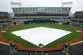 OAKLAND, CA - APRIL 16: A tarp covers the infield as rain falls before the game between the  Houston Astros and the Oakland Athletics at Oakland Alameda Coliseum on April 16, 2017 in Oakland, California. The game was postponed to a future date do to the weather. (Photo by Lachlan Cunningham/Getty Images)
