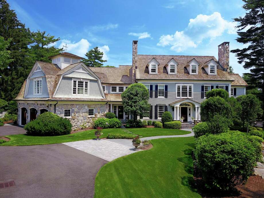 The gray shingle and stone colonial at 79 Devonwood Lane has an English pub-style bar, a built-in aquarium, outdoor fireplace, an in-ground heated swimming pool. Photo: Contributed Photos