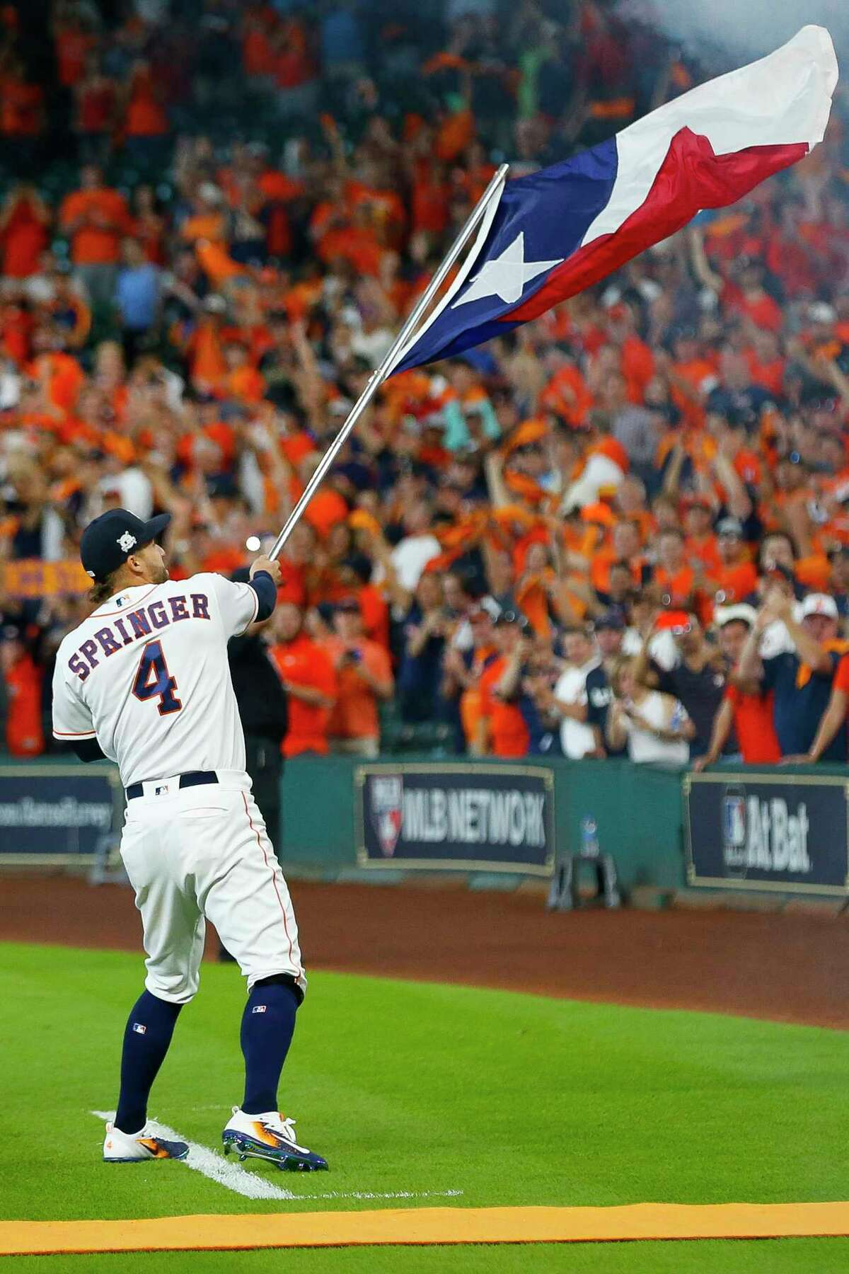 Houston Astros center fielder George Springer waves a Texas flag before the beginning of Game 1 of the ALDS at Minute Maid Park on Thursday, Oct. 5, 2017, in Houston.