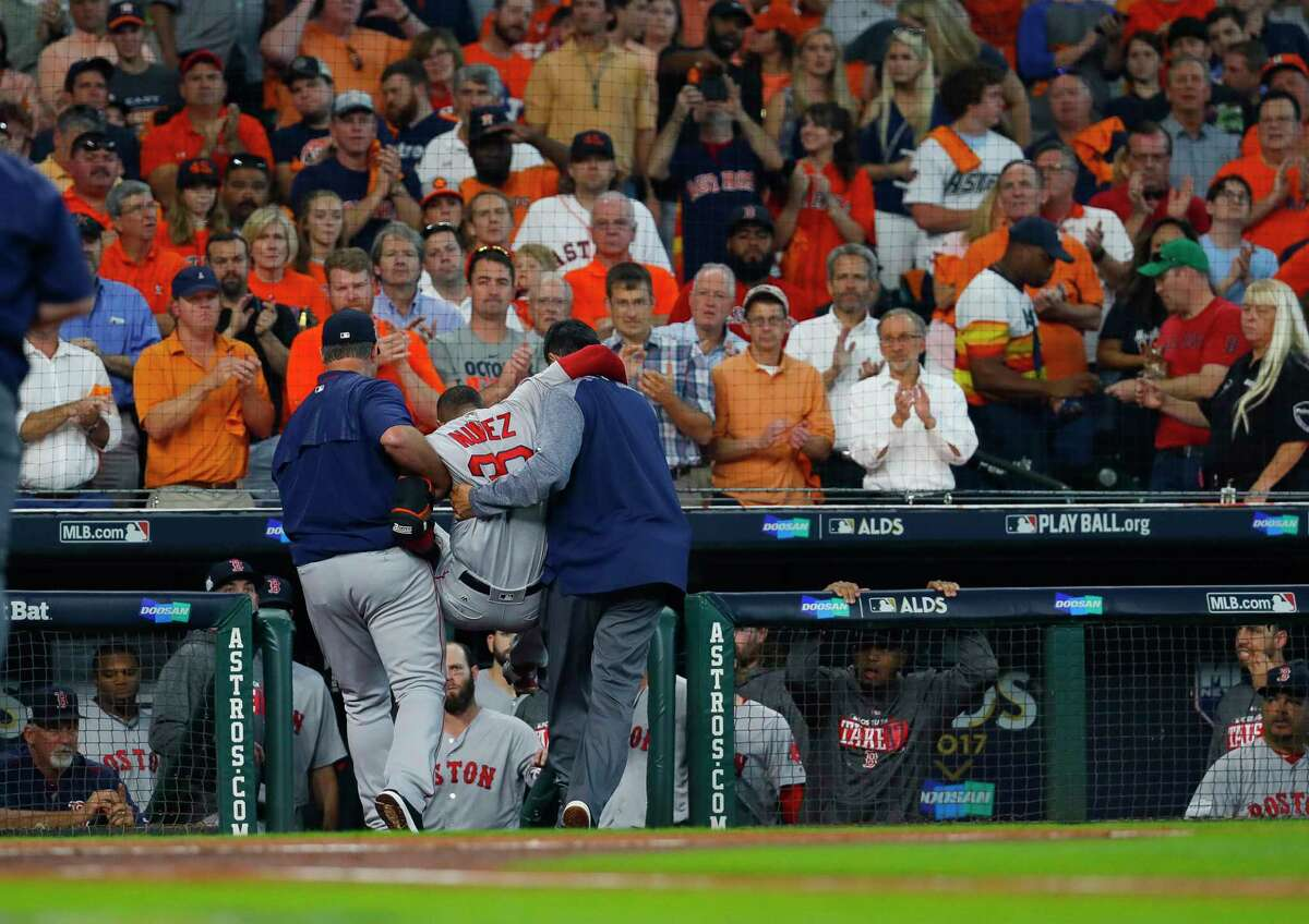 Boston Red Sox second baseman Eduardo Nunez is carried off the field during the first inning of Game 1 of the ALDS at Minute Maid Park on Tuesday, Oct. 3, 2017, in Houston.