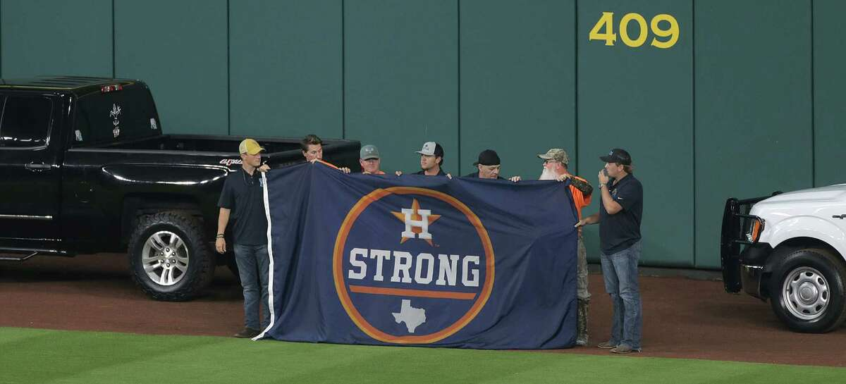 Members of the Cajun Navy hold a Houston Strong flag that will be flown at Minute Maid Park before ALDS Game 1 between the Boston Reds Sox and the Houston Astros at on Thursday, Oct. 5, 2017, in Houston.