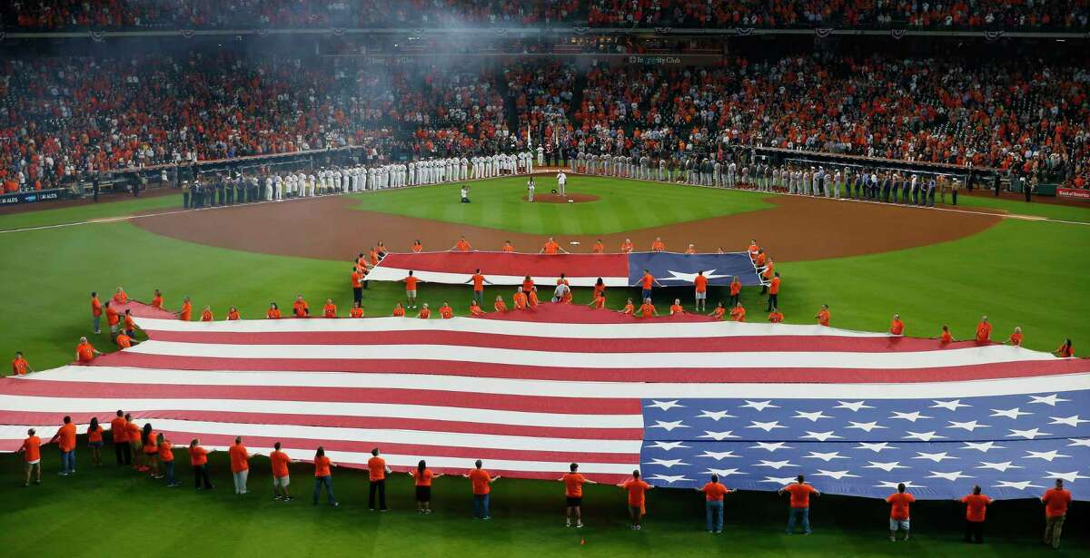 An American flag is unfurled on the field for the national anthem before the Houston Astros take on the Boston Red Sox during the first game of the American League Divisional Series at Minute Maid Park Thursday, Oct. 5, 2017 in Houston.