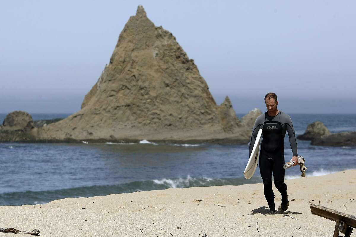 Surfer Danson Drummer of Mill Valley walks past the iconic Pelican Rock after surfing at Martin's Beach in Half Moon Bay, CA, Thursday May 15, 2014.
