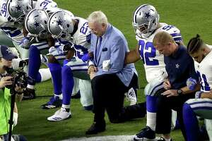 The Dallas Cowboys, led by owner Jerry Jones, center, take a knee prior to the national anthem prior to an NFL football game against the Arizona Cardinals on Monday. The move drew both praise and criticism.