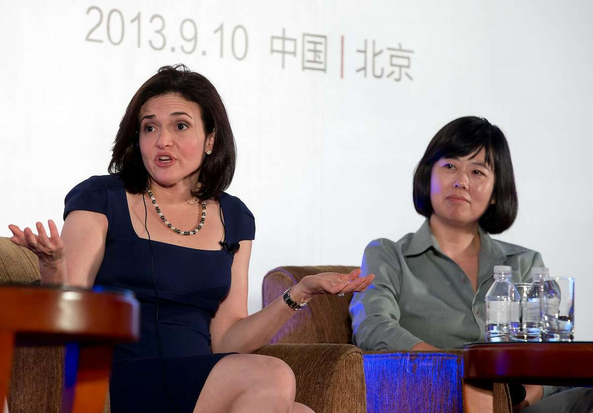 """Facebook Chief Operating Officer Sheryl Sandberg, left, speaks next to Wang Xin, Chief Operating Officer of Sohu, during the dialogue session on """"Women in Leadership and the Future of Online Business"""", hosted by Cheung Kong Graduate School of Business (CKGSB) and CITIC Press Corporation and Xinrui New Media at a hotel in Beijing Tuesday, Sept. 10, 2013. (AP Photo/Andy Wong)"""