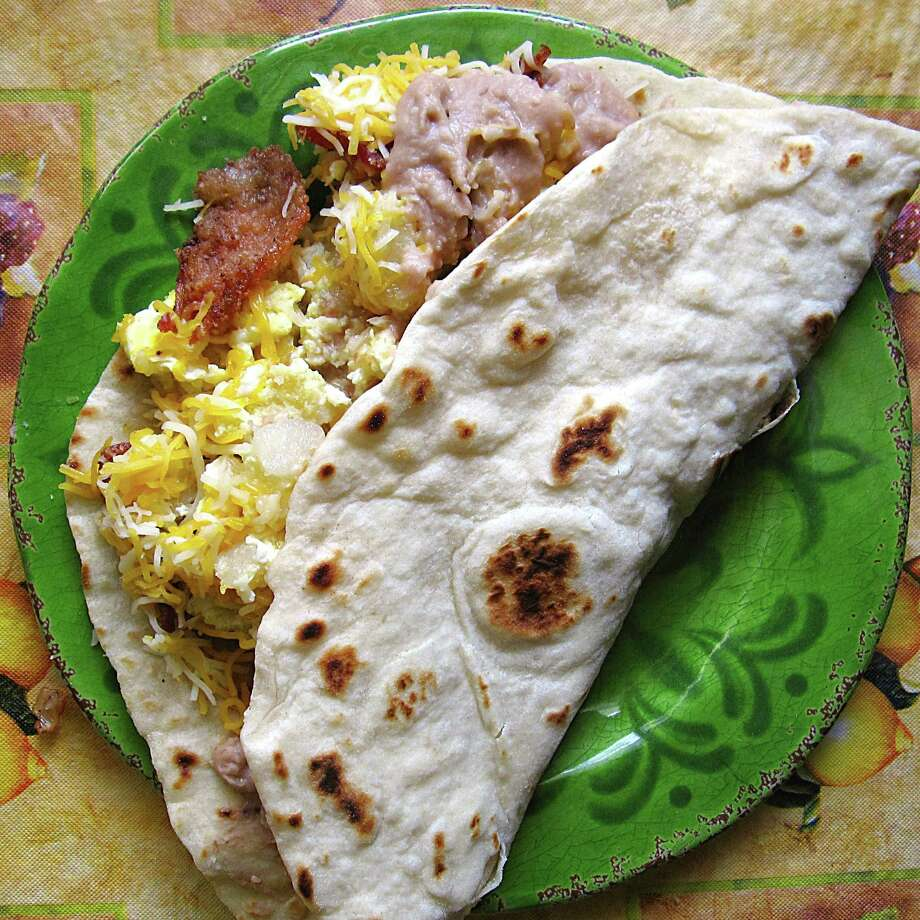 Breakfast Monster taco with eggs, bacon, beans, cheese and potatoes on a handmade flour tortilla from Arturo's Cafe. Photo: Mike Sutter /San Antonio Express-News