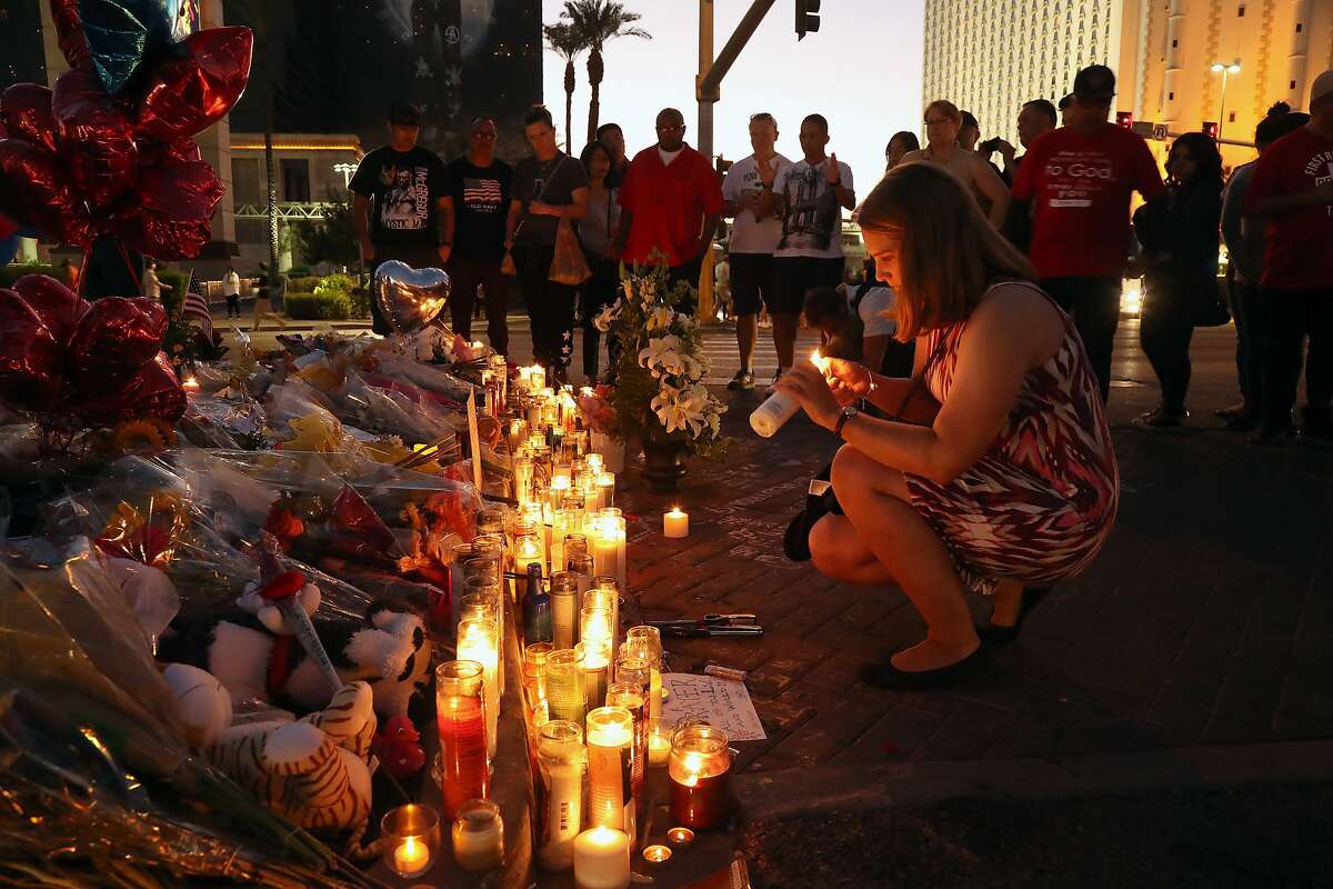 A woman lights a candle on Wednesday evening, Oct. 4, 2017, at a sidewalk memorial in Las Vegas to the victims of the mass shooting on Sunday night. Investigators on Thursday were still piecing together the life of the gunman, Stephen Paddock, who killed 58 concertgoers in Las Vegas, and remained at a loss to explain what drove him to commit the massacre. (Jim Wilson/The New York Times)