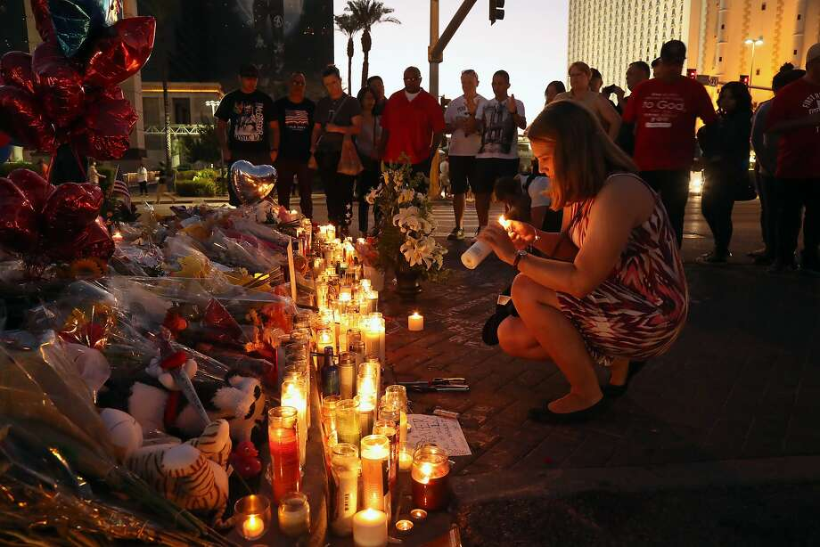 A woman lights a candle on Wednesday evening, Oct. 4, 2017, at a sidewalk memorial in Las Vegas to the victims of the mass shooting on Sunday night. Photo: JIM WILSON, NYT