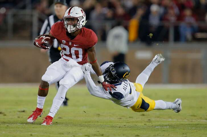 Stanford's Bryce Love, 20 picks up a first quarter first dfown as he is chased by California's Darius Allensworth, 2 as Stanford takes on California in the 118th Big Game at Stanford Stadium, on Sat. November 21, 2015, in Stanford, Calif.