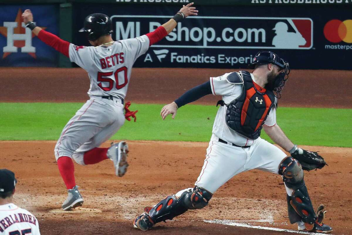 Boston Red Sox right fielder Mookie Betts flies past Houston Astros catcher Evan Gattis as he scores as the Houston Astros take on the Boston Red Sox during the fourth inning of the first game of the American League Divisional Series at Minute Maid Park Thursday, Oct. 5, 2017 in Houston.