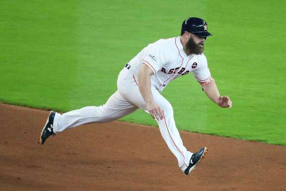 Houston Astros catcher Evan Gattis starts to slide into second after hitting a double as the Houston Astros take on the Boston Red Sox during the fourth inning of the first game of the American League Divisional Series at Minute Maid Park Thursday, Oct. 5, 2017 in Houston.