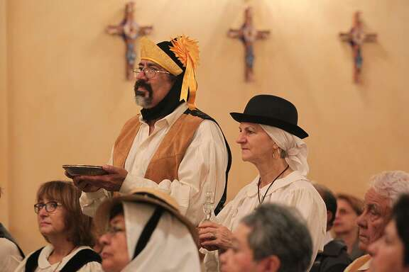 Richard and Kyle Contreras bring forth the bread and wine as Canary Island Descendants Association of San Antonio members gather in celebration of Our Lady of Candelaria at Mission Concepcion, Feb. 1, 2015.