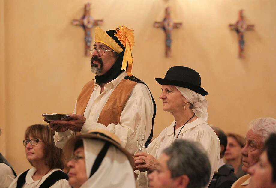 Richard and Kyle Contreras bring forth the bread and wine as Canary Islands Descendants Association of San Antonio members gather in celebration of Our Lady of Candelaria at Mission Concepcion in 2015. The virgin is the patroness of the Canary Island, and her feast day is Feb. 2. Arriving in the area in 1731, the Canary Islands played a key role in San Antonio's history, creating the first organized civil government in Texas. Photo: Jerry Lara /San Antonio Express-News / © 2015 San Antonio Express-News