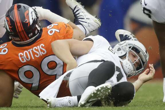 Oakland Raiders quarterback Derek Carr grabs his back after being sacked by Denver Broncos defensive ends Adam Gotsis during the second half of an NFL football game Sunday, Oct. 1, 2017, in Denver. Carr left the game with a back spasm. (AP Photo/Jack Dempsey)