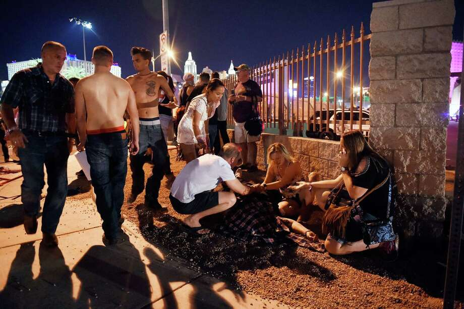 Concertgoers tend to the wounded outside the grounds of the Route 91 Harvest festival Sunday in Las Vegas. An apparent lone gunman killed 58 people and wounded hundreds more. Photo: David Becker, Stringer / 2017 Getty Images