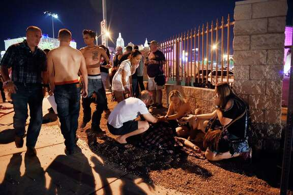 Concertgoers tend to the wounded outside the grounds of the Route 91 Harvest festival Sunday in Las Vegas. An apparent lone gunman killed 58 people and wounded hundreds more.