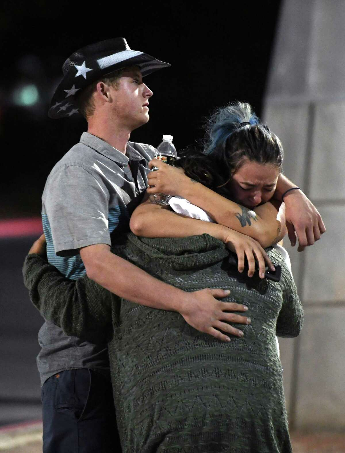 People hug and cry after Sunday's mass shooting in Las Vegas.