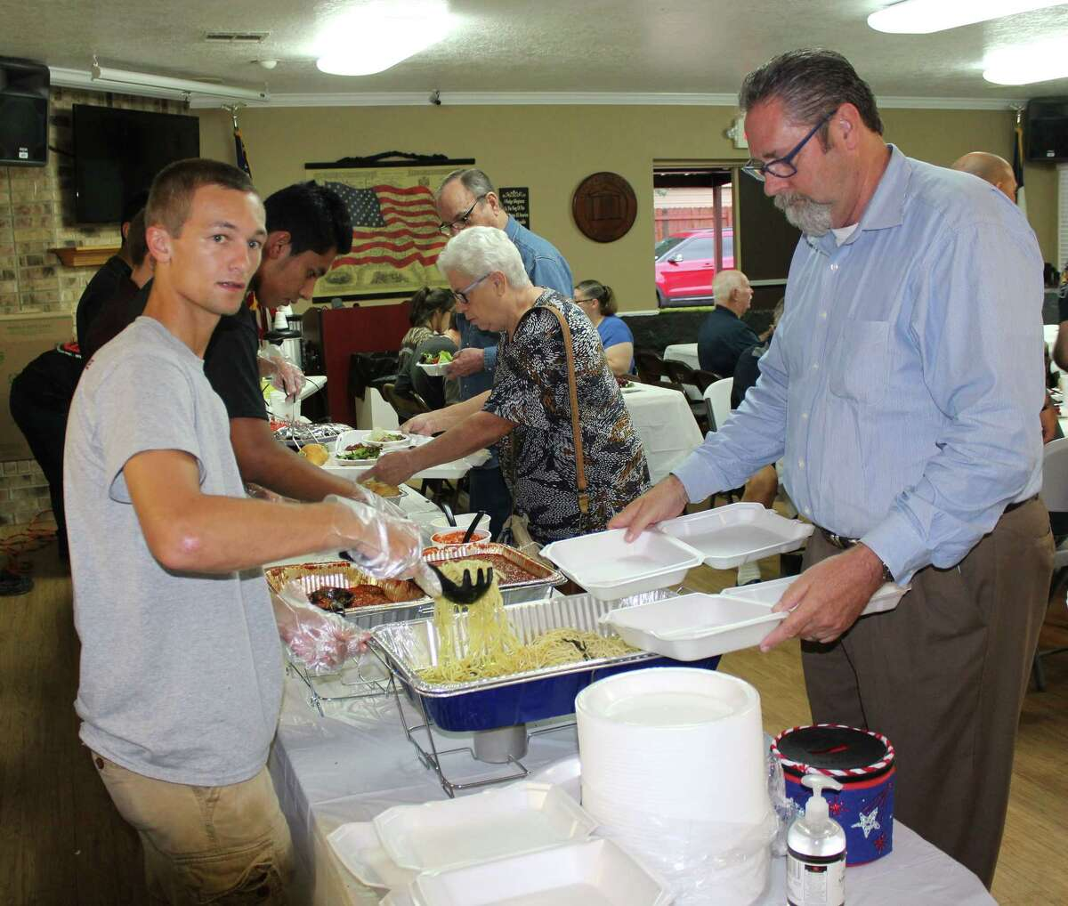 Members of the Roman Forest Police Explorers (left) serve the Roman Forest public at the National Night Out spaghetti dinner held at city hall. The Roman Forest Police Explorers are a group of Boy Scouts that are given opportunities to learn about law enforcement.