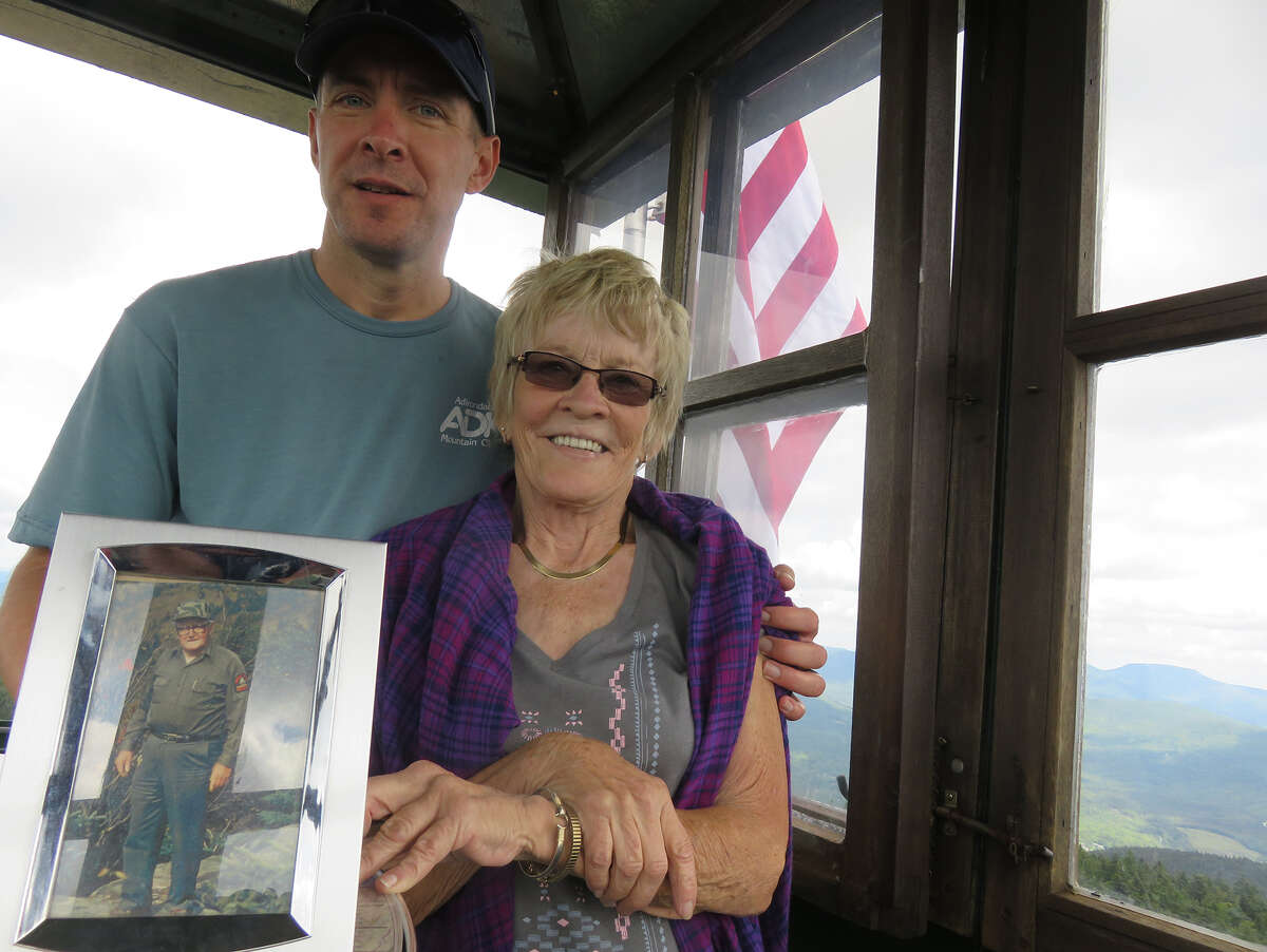 Herb Terns and Diann Terns-Thorpe stand in the Hunter Mountain Fire Tower with a photo of Bill Byrne, their grandfather and father, respectively. (Courtesy of Herb Terns)