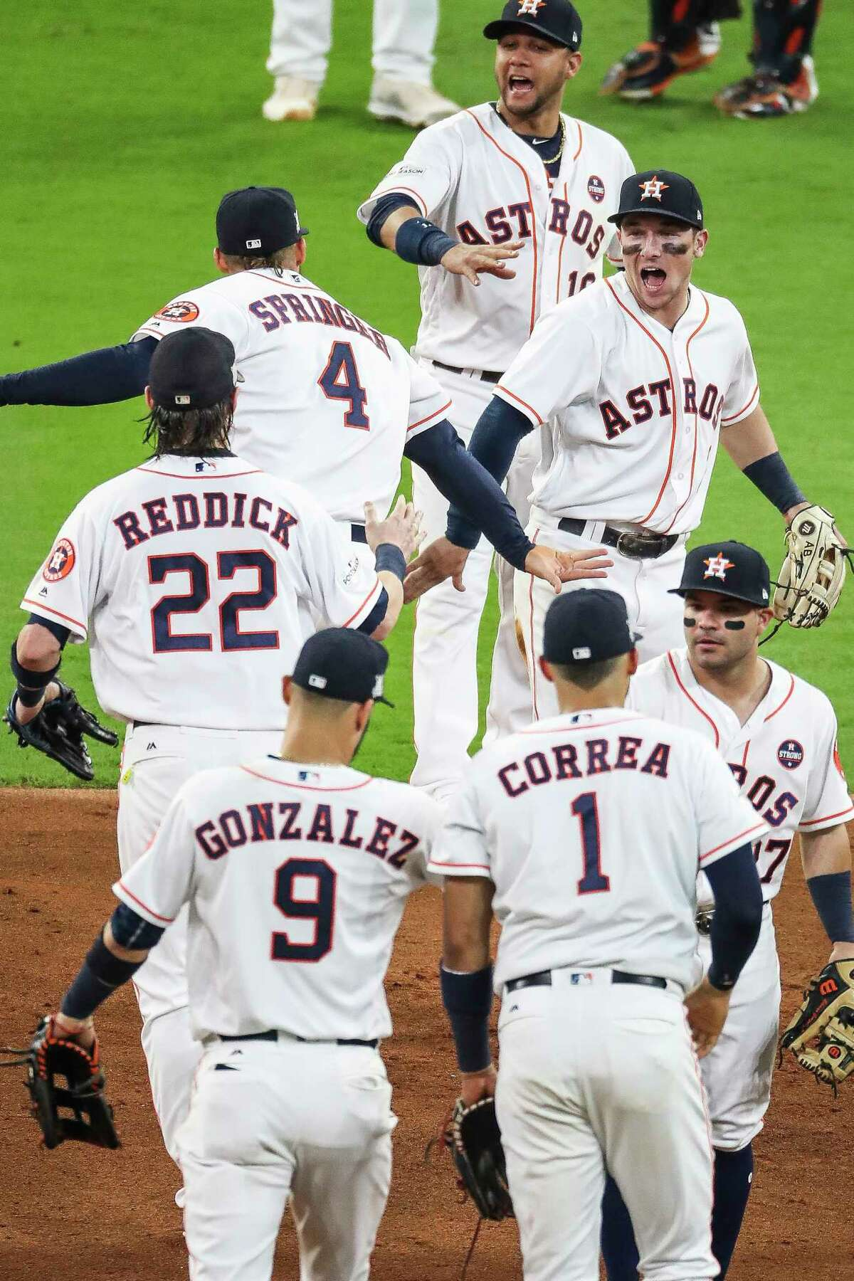 Houston Astros center fielder George Springer and third baseman Alex Bregman high five as they celebrate with teammates after beating the Boston Red Sox 8-2 in the first game of the American League Divisional Series at Minute Maid Park Thursday, Oct. 5, 2017 in Houston.