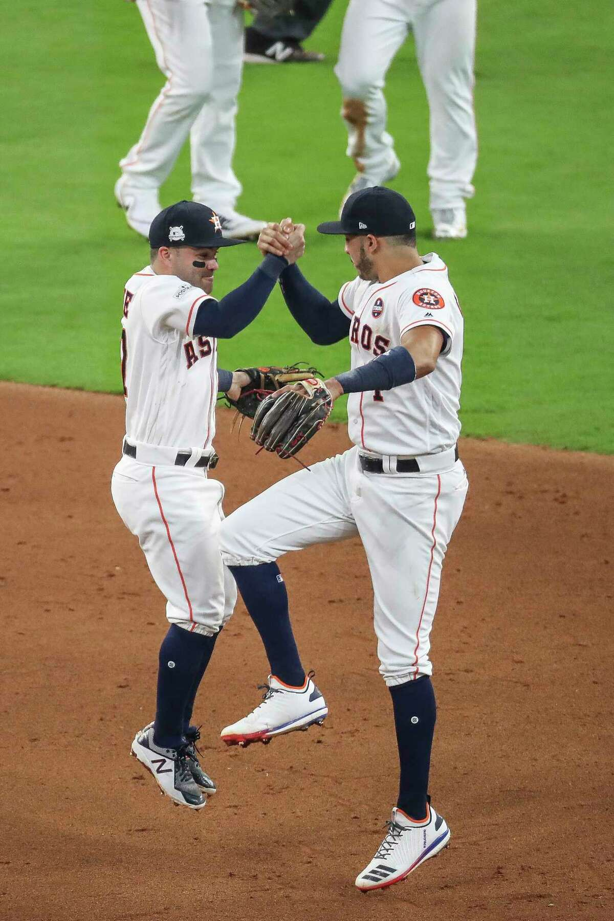 Houston Astros second baseman Jose Altuve and shortstop Carlos Correa celebrate after beating the Boston Red Sox 8-2 in the first game of the American League Divisional Series at Minute Maid Park Thursday, Oct. 5, 2017 in Houston.