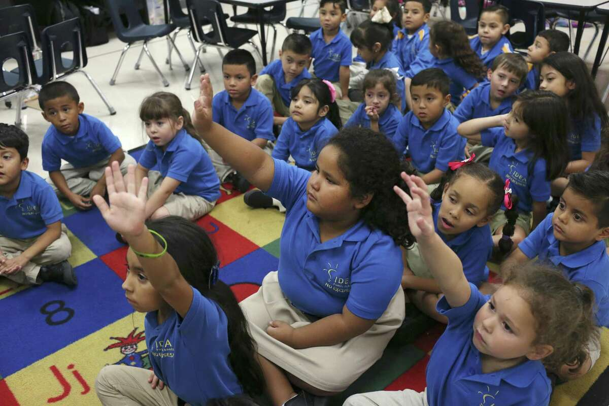 Students including, Aulyana Garcia, center, raise their hands during a kindergarten English lesson at IDEA Monterrey Park on the city's West Side, Thursday, Oct. 5, 2017. IDEA Public Schools received a $67 million grant from the U.S. Department of Education that will allow it to expand.