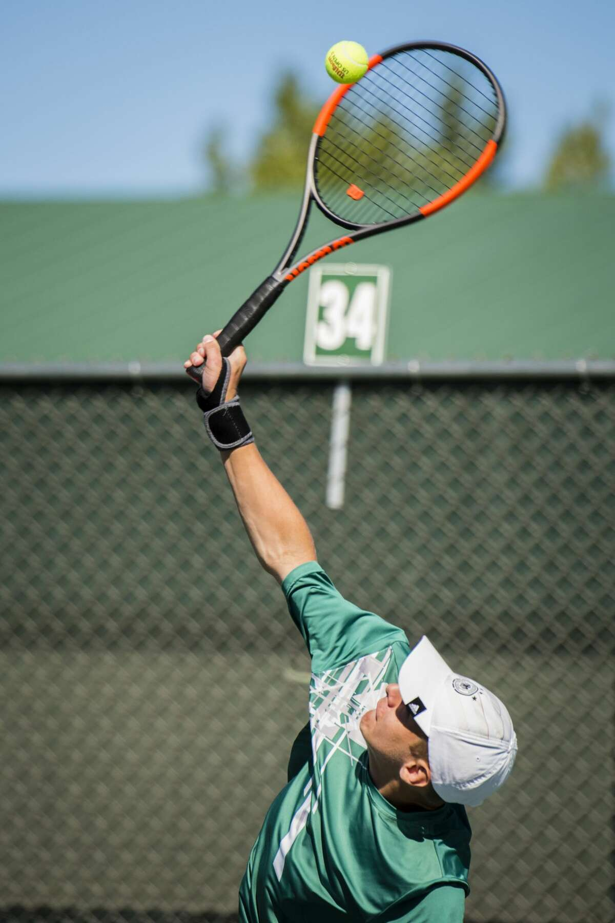 Senior Kevin Kraef, half of Dow's number three doubles pair, serves the ball during the Saginaw Valley Boys Tennis Tournament on Thursday, Oct. 5, 2017at the Greater Midland Tennis Center. (Danielle McGrew Tenbusch/for the Daily News)
