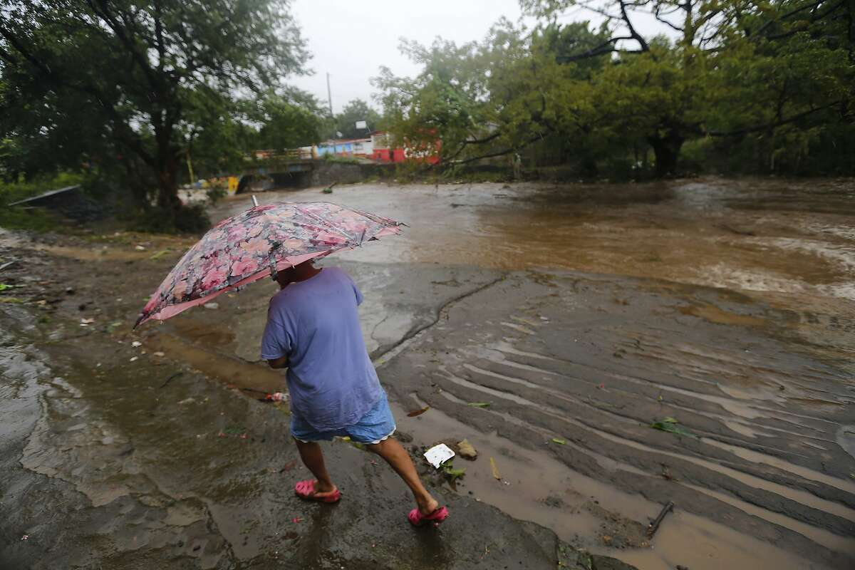A woman walks in the rain near the flooded Masachapa River following the passage of Tropical Storm Nate in the city of Masachapa, about 60km from the city of Managua on October 5, 2017. A tropical storm sliding north along Central America Thursday has unleashed heavy rains killing at least nine people in Costa Rica and Nicaragua, with forecasters predicting it could strengthen into a hurricane headed for the United States. / AFP PHOTO / INTI OCONINTI OCON/AFP/Getty Images