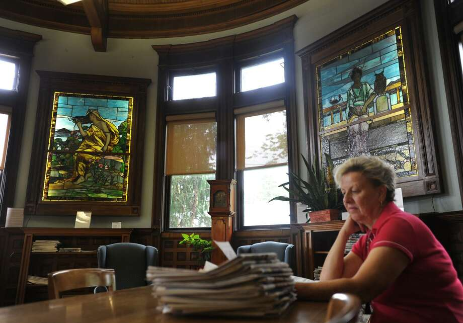 Christa Kozlowsky, of Shelton, looks over newspapers in front of recently restored stained glass panels in the 1895 reading room of the Plumb Memorial Library in Shelton, Conn. on Tuesday, September 6, 2016. Stored for years in the library attic, the panels were originally part of a dividing wall which was removed. The stained glass was restored by Shelton company The Glass Source that does similar work for churches and universities. Photo: Brian A. Pounds / Hearst Connecticut Media / Connecticut Post