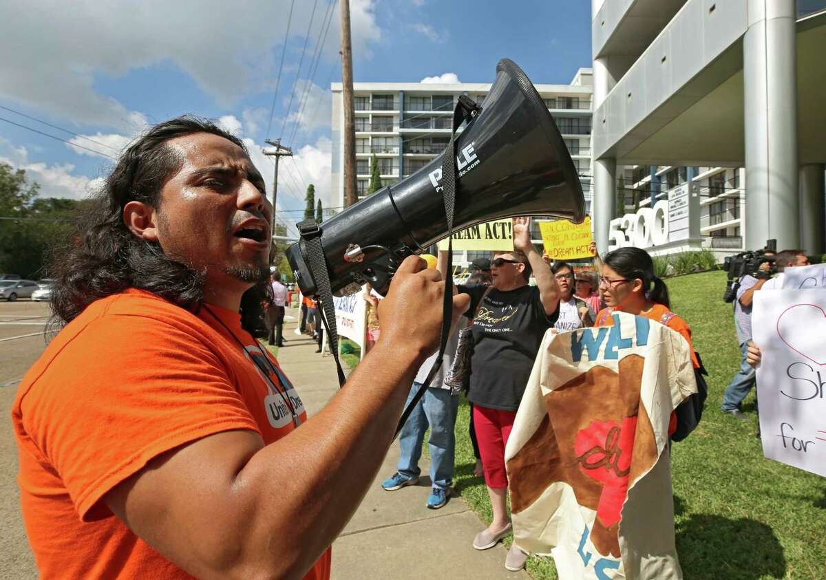 Oscar Hernandez, with United We Dream Houston, leads protesters Thursday in a chant outside U.S. Sen. John Cornyn's Houston office to voice their support for legislation protecting