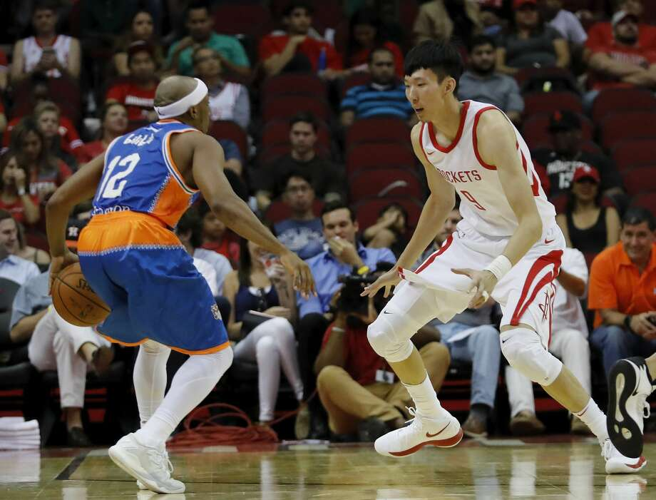 HOUSTON, TX - OCTOBER 05:  Zhou Qi #9 of Houston Rockets defends Josh Akognon #12 of Shanghai Sharks in the second quarter at Toyota Center on October 5, 2017 in Houston, Texas.  NOTE TO USER: User expressly acknowledges and agrees that, by downloading and or using this Photograph, user is consenting to the terms and conditions of the Getty Images License Agreement.  (Photo by Tim Warner/Getty Images) Photo: Tim Warner/Getty Images