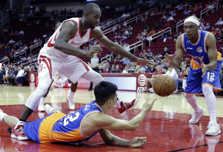 Houston Rockets forward Luc Mbah a Moute (12) tries to break up the pass from Shanghai Sharks forward Zhai Yi (22) to Josh Akognon (12) in the first half of an NBA exhibition basketball game Thursday, Oct. 5, 2017, in Houston. (AP Photo/Michael Wyke) Photo: Michael Wyke/Associated Press