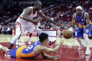 Houston Rockets forward Luc Mbah a Moute (12) tries to break up the pass from Shanghai Sharks forward Zhai Yi (22) to Josh Akognon (12) in the first half of an NBA exhibition basketball game Thursday, Oct. 5, 2017, in Houston. (AP Photo/Michael Wyke)