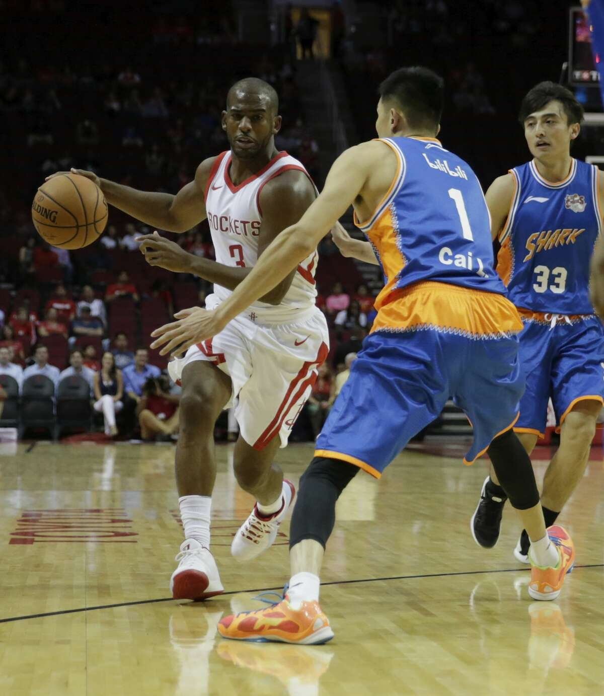 HOUSTON, TX - OCTOBER 05: Chris Paul #3 of Houston Rockets drives the ball in the first quarter defended by Cai Liang #1 of Shanghai Sharks at Toyota Center on October 5, 2017 in Houston, Texas. NOTE TO USER: User expressly acknowledges and agrees that, by downloading and or using this Photograph, user is consenting to the terms and conditions of the Getty Images License Agreement. (Photo by Tim Warner/Getty Images)