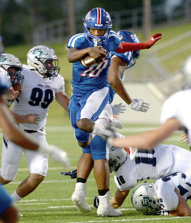 West Brook's Bralin Adams leaps over College Park's defense as he carries the ball during Thursday's homecoming game. Photo taken Thursday, October 5, 2017 Kim Brent/The Enterprise Photo: Kim Brent / BEN