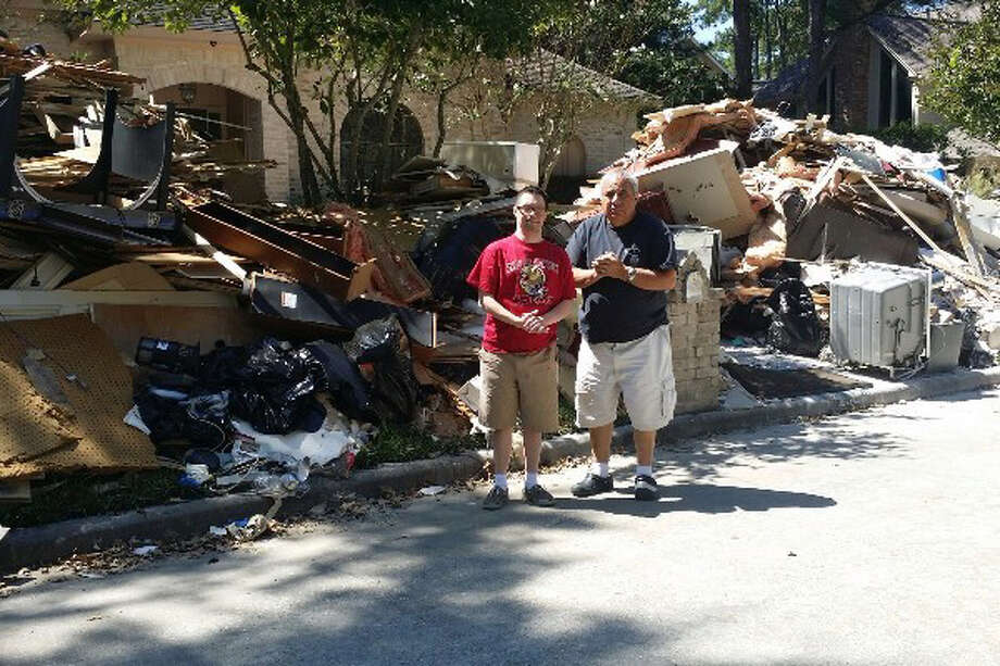 Matthew Breitling and his father Sam Breitling stand outside the house they rented in Kingwood, which flooded during hurricane Harvey, damaging the furniture and displacing their family. Photo: Courtesy Of JoAnn Breitling