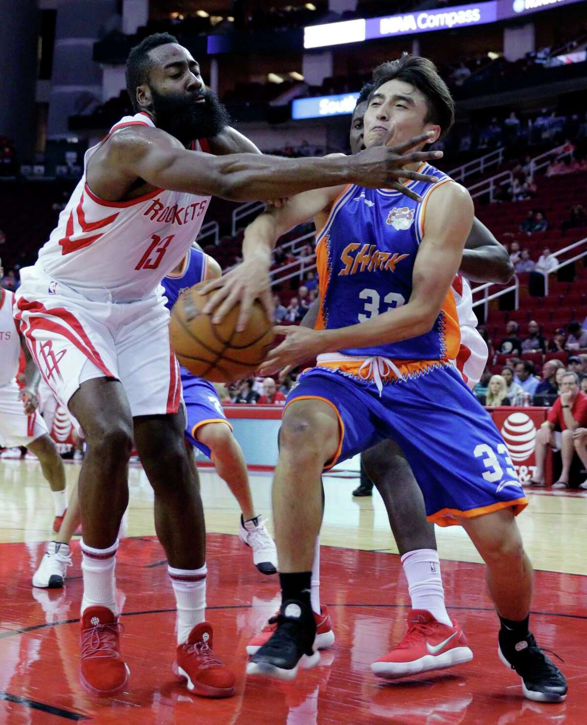 The Rockets' James Harden (13) defends a pass from Shanghai Sharks guard Luo Hanchen (33) in the first half Thursday. Harden was 4-for-11 for nine points
