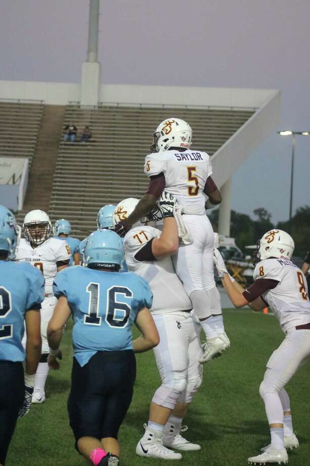Tyrek Saylor leaps into the arms of Jeremiah Webb after Saylor scores his first touchdown of the night. Saylor finished with 156 yards rushing. Photo: Robert Avery