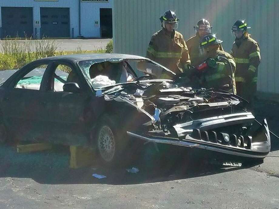 Gladwin firefighter Katie Brubaker demonstrates using the Jaws of Life, while cutting a 'dummy' out of a donated sedan Saturday during the department's 14th annual open house. (Photo by Tereasa Nims)