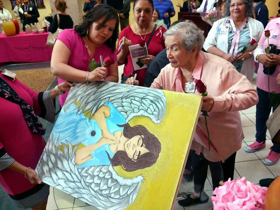A los sobrevivientes de cáncer y a miembros de familia se les pidió que firmaran el Ángel de Esperanza de este año pintado por Krystal Hinojosa, estudiante de octavo grado en la Escuela Secundaria Clark, en el Laredo Medical Center, el jueves 5 de octubre de 2017. Photo: Cuate Santos /Laredo Morning Times / Laredo Morning Times