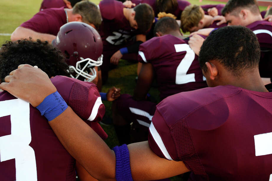 Silsbee junior varsity football players bow their heads in prayer before their game on Thursday evening. The players wore purple sweatbands and wrist tape in memory of JV cheerleader Tristan Dilley, whose favorite color was purple. Dilley was killed on Sunday.  Photo taken Thursday 10/5/17 Ryan Pelham/The Enterprise Photo: Ryan Pelham / ©2017 The Beaumont Enterprise/Ryan Pelham