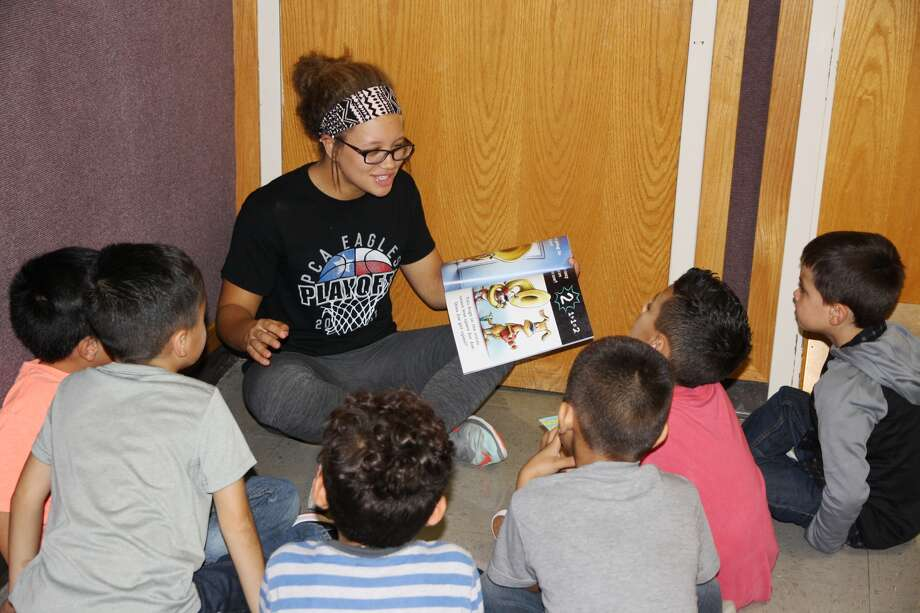 Hale County Junior Literacy Council member K'Lee Roberts on Tuesday reads a book to La Mesa first grade students participating in the Hale County Literacy Council's Read First afterschool program.